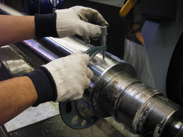 Machinist using micrometer on hydraulic cylinder
